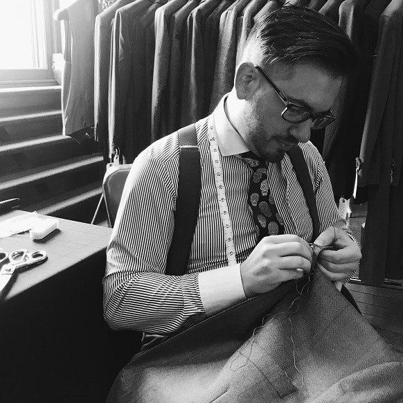 Bespoke Tailor threading the button holes on a Bespoke Jacket