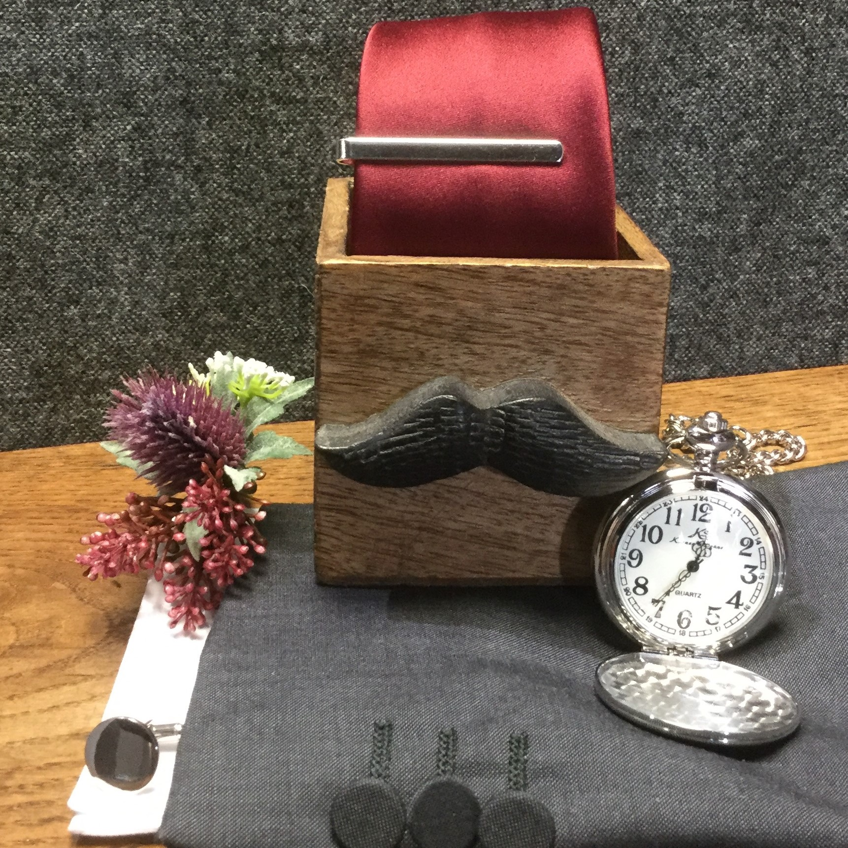 Silver Pocketwatch with a silver tie bar and silver cufflinks and charcoal wedding suit