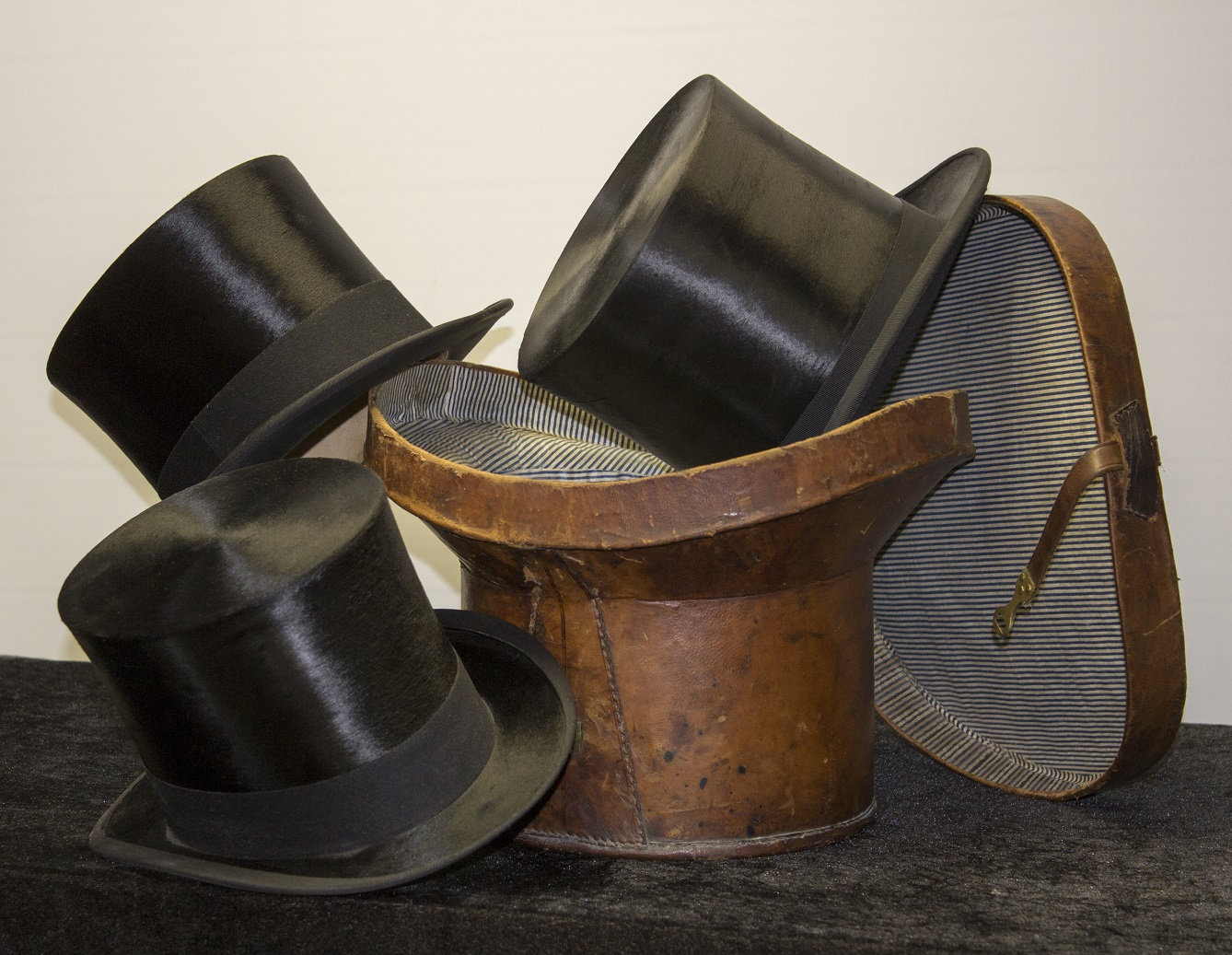 A selection of antique silk black top hats along with a traditional leather hat box